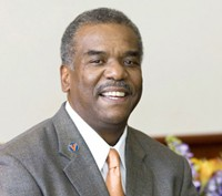 Dr. Marcus Martin smiles in a suit and tie with a UVA pin on his lapel